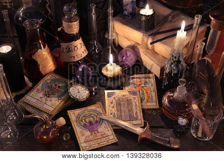 Still life with the tarot cards, knife, book, magic objects and evil candles on witch table. Halloween concept, black magic ritual or spell with occult and esoteric symbols, divination rite