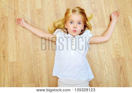 Cute joyful girl lying on a floor at home.