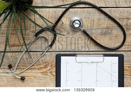 new stethoscope on wooden table with cardiogram and flower top view