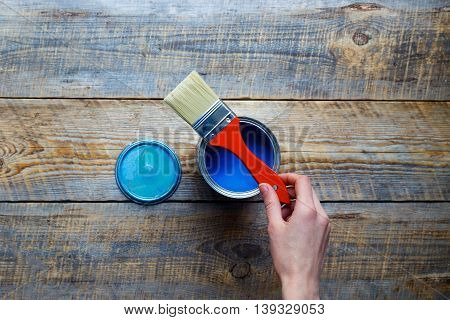 painting with open can of blue paint and red brush in hand on wooden background top view