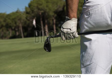 golf player hand and driver close up  from back with course in background  at beautiful sunny day