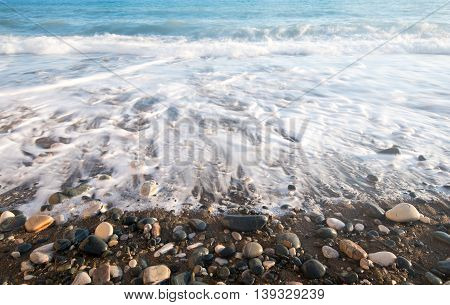 Sea waves crashing on the shore and flowing above seashore pebbles.