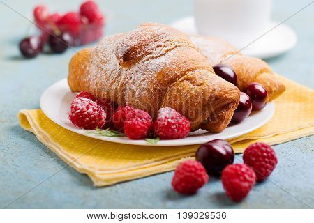 Freshly baked croissant with berries for breakfast,selective focus
