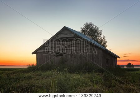 Sunset Behind A Barn And A Birch