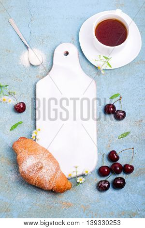 Breakfast or dessert set. Freshly baked croissants with cherry and cup of tea over blue background, white wooden board in center. Top view, copy space