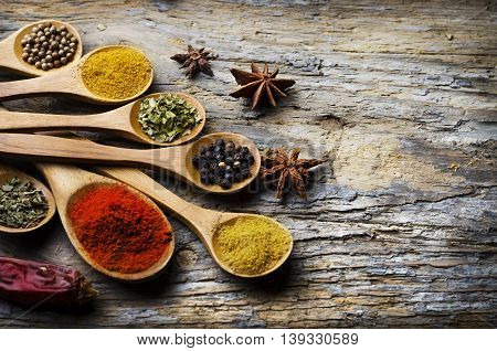 Spices in Wooden spoon on a wooden rustic background