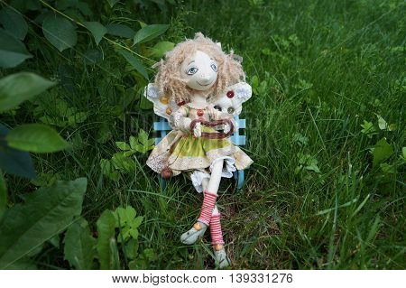 Toy little fairy unwinds strands, sitting on a bench under a tree