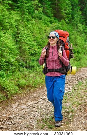 happy woman hiker trekking on trail in mountains. Girl hiker walking on dirt road in forest. Healthy lifestyle adventure camping on hiking trip. Hiker walking with backpack on hiking trail in forest nature on mountain path