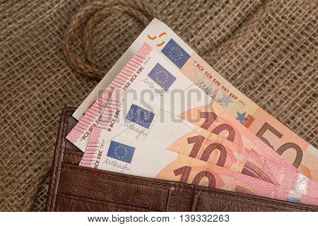 Euro banknotes in a purse on the textile background