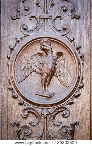 Eagle engraved on the wooden portal of a medieval church.