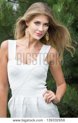 Portrait of pretty young blond longhair woman with jewerly outdoors.