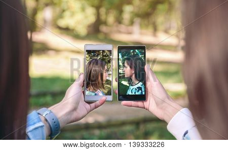 Women friends showing smartphones with their side view portraits photos taked over a forest background