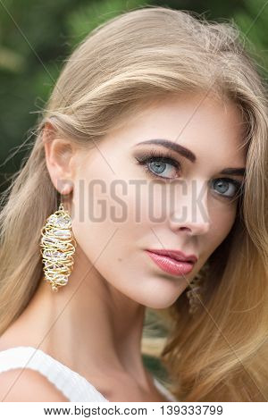 Close-up portrait of beautiful young blond longhair woman with jewerly outdoors.