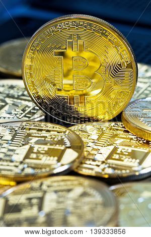 Photo Golden Bitcoins (new virtual money ) Close-up on a blue background.