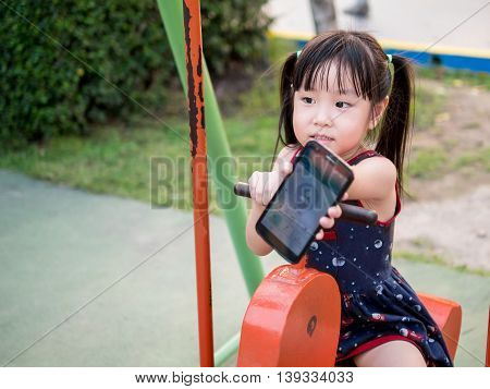 Happy kid asian baby child playing on playground show the mobile phone
