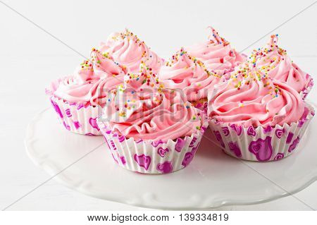 Pink birthday cupcakes on cake stand. Birthday cupcake with pink whipped cream. Homemade cupcakes served for party.