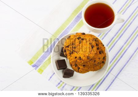 Cup of tea with chocolate chip cookies and dark chocolate. Breakfast cookies and tea cup. Tea time with cookies.