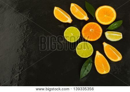 Detox concept with lemon orange and lime on black background. Healthy eating concept with ripe mixed citrus. Lime lemon and orange fruit background.
