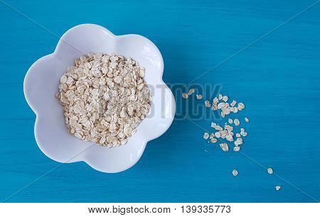a bow of oatmeal on a turquoise wooden backgrounf