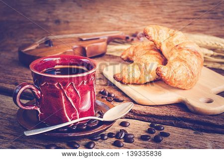 Continental breakfast with coffee and croissant on wooden