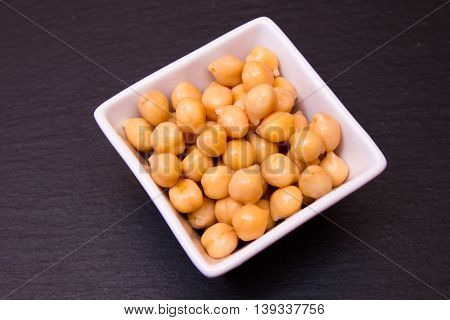 Boiled chickpeas on a square bowl on a slate top seen from above