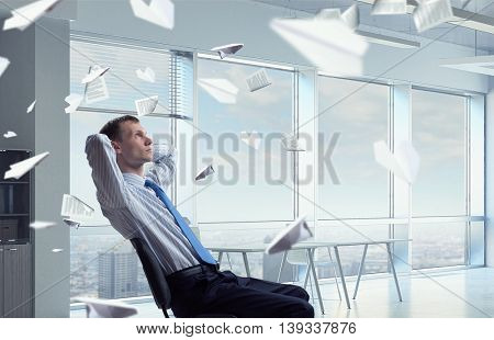 Businessman relaxing in his office mixed medi . Mixed media