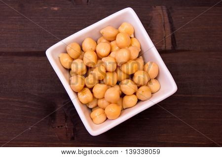 Boiled chickpeas on a square bowl on a wooden table seen from above