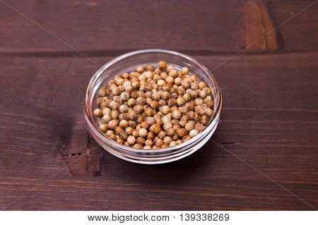 Coriander seeds on a bowl on a wooden table