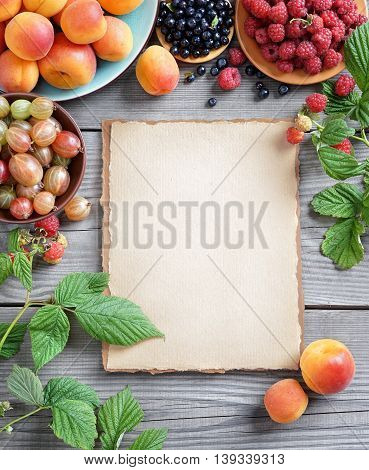 Deluxe berries background. Open recipe book with apricots, raspberries, bilberry, gooseberries on wooden table. Copy space, top view, high resolution product.