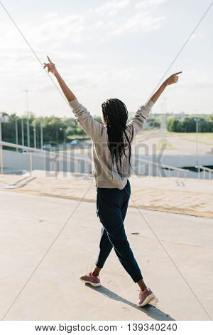 Silhouette of happy african american girl raised her hands up to the sun, standing at urban background.