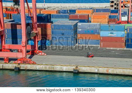 Barcelona Spain - June 2 2016: View of commercial port with its colorful rail cranes containers and stacker lift truck