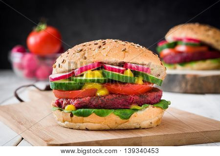 Veggie beet burger on white table and black slate background