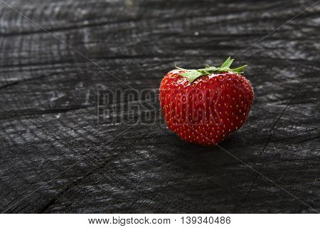 Red fresh strawberry on black rustic wood background. One natural ripe organic berry with peduncle on wooden surface, view with copy space