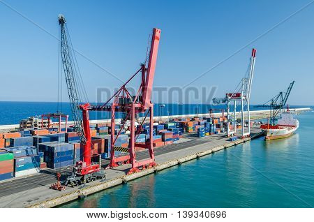 Barcelona Spain - June 2 2016: View of commercial port with its colorful rail cranes containers and a boat