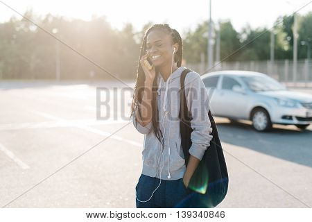 Beautiful african american woman walkin with hand in pocket talking on smart phone in city, looking away, outdoors sunny exterior.
