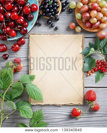 Healthy food background. Mix berries and old paper on wooden table. Copy space for your text. Top view, high resolution product. Harvest concept.