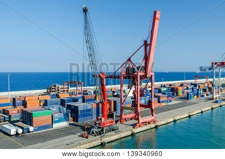 Barcelona Spain - June 2 2016: View of commercial port with its colorful rail cranes and containers