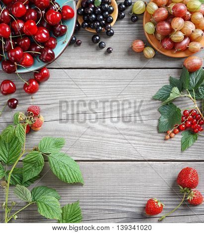 Organic food background. Cherry, gooseberry, currant, raspberry, strawberry and green leaves on wooden table. Copy space, top view, high resolution product.
