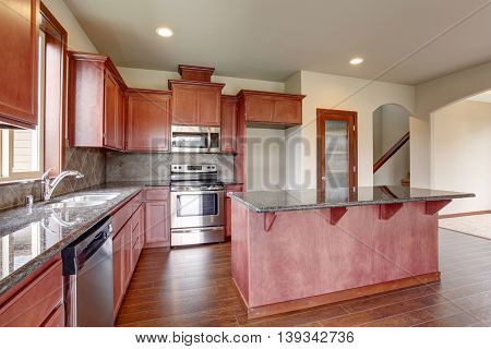 Kitchen With Bright Wooden Cabinets, Steel Appliances And Granite Tops