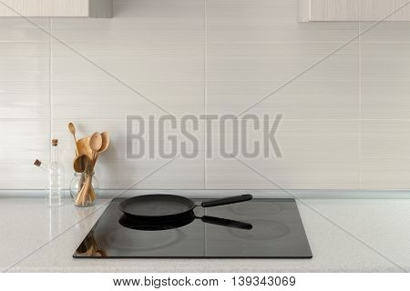 Pot and wooden spoons in modern kitchen with induction stove