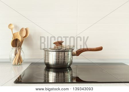 Open saucepan and wooden spoons in modern kitchen with induction stove