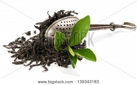 Dry black tea vintage tea strainer and fresh tea leaves isolated on white background.