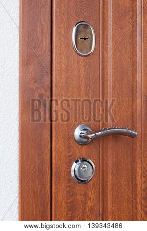 Detail of Modren style metallic door handle on wooden door
