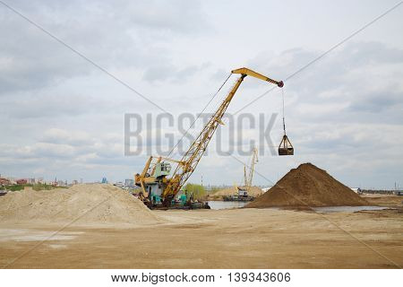 Cranes work at dock on River and huge piles of sand at spring day
