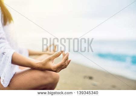 Young girl is meditating on the beach