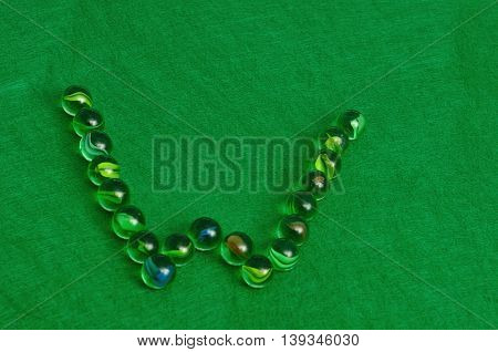 The letter W made out of marbles on a green background