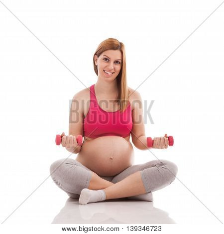 Fitness pregnant lady with dumbbells isolated, close up