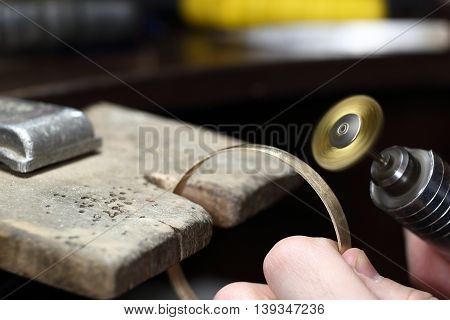 Jeweller Working With Bracelet By Polishing Motors Tool. Jewelry Workplace