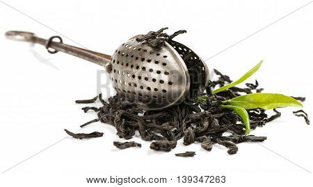 Dry black tea and fresh tea leaves and a vintage tea strainer isolated on white background.