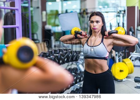 Fit woman looking at mirror, exercising with kettlebell in gym.